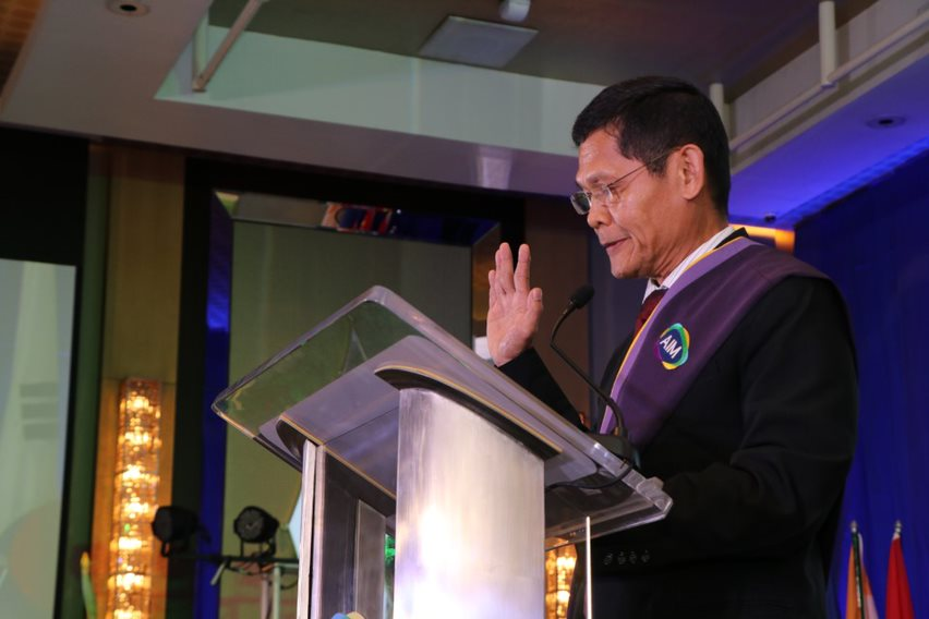 Mr. Diosdado Domingo, MBM 1988, leading the oath taking during the induction of graduates to the AIM Alumni Association